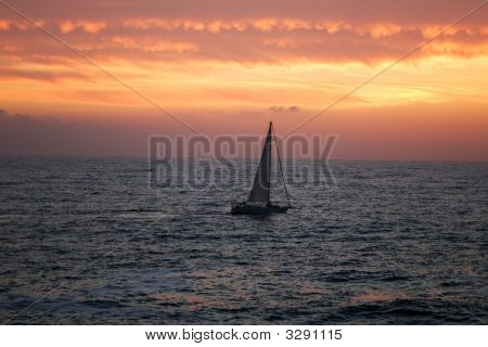 The Sea, Yacht And Clouds On A Sunset