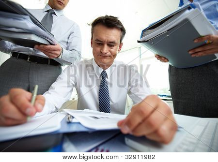 Responsible accountant doing financial reports being surrounded by business partners with huge piles of documents