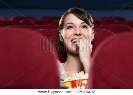 Smiling young woman with popcorn watching a movie