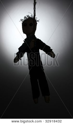 Hanged doll voodoo boy-groom on grey background