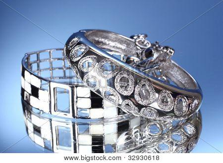 Beautiful silver bracelets on blue background