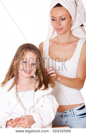 Smiling girl with beads and earring on, and her mother brushing hair