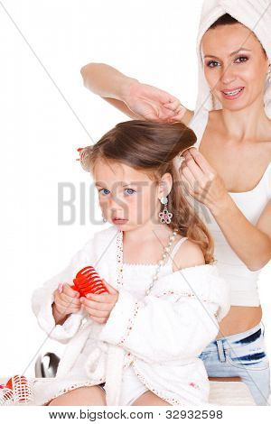 Young mother styling daughter's hair
