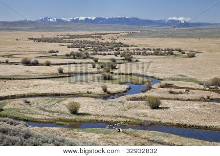 Illinois River meanders through Arapaho National Wildlife Refuge, North Park near Walden, Colorado, early spring scenery with some snow in distant mountains