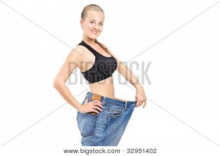 A happy weight loss female holding her old jeans isolated on white background