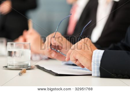 Business - people sitting in a meeting, close-up on hands and man in the front