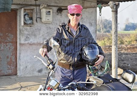Caucasian Biker Outside Shack In Hinterlnads India
