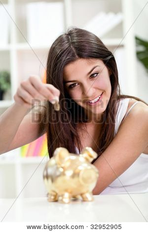Teenager girl putting coin in golden piggybank banking, investment,