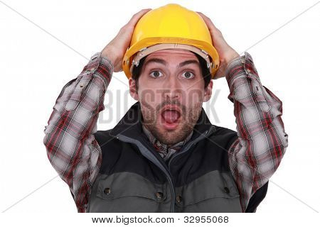 Worker holding her hands to her head