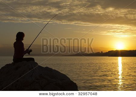 Happy girl fishes at sunset
