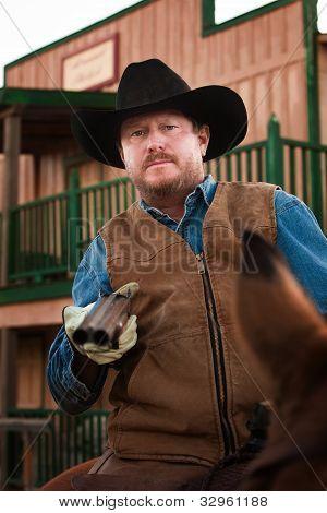 Armed Cowboy On Horseback