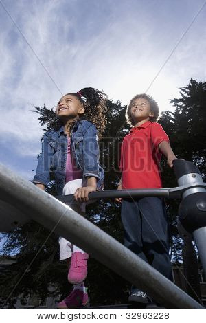 African American children playing on jungle gym