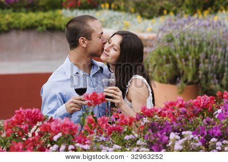 Hispanic couple kissing with wine