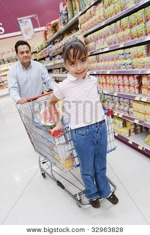 Hispanic father and daughter grocery shopping