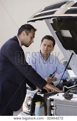 Hispanic man talking to car salesman