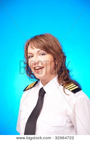 Beautiful woman pilot wearing uniform with epauletes standing on blue background