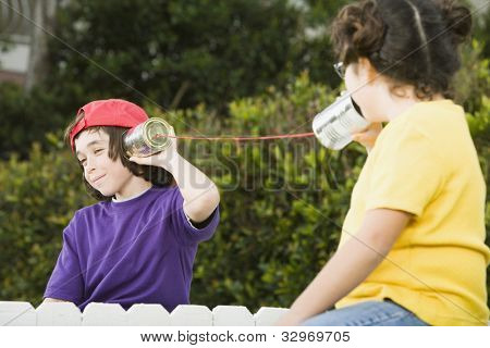 Mixed Race children talking with cans and string