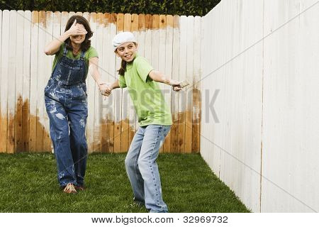 Mother and daughter painting fence