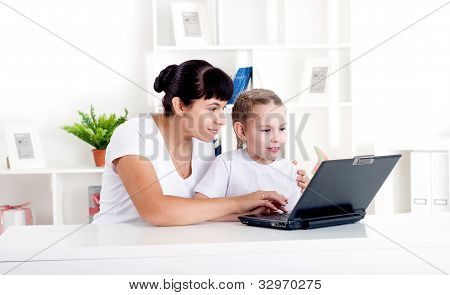 Mom and daughter are working together for a laptop