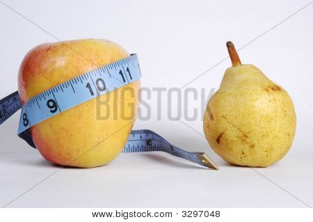 Apple Wrapped In Blue Tape Measure Next To A Pear.