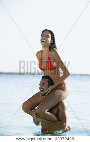 South American woman sitting on boyfriend's shoulders