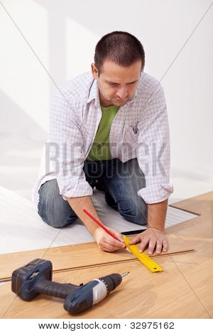 Man Laying Laminate Flooring