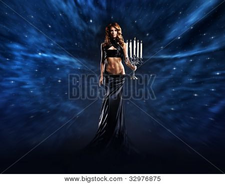 Fashion shoot of beautiful woman in a long dress over space background