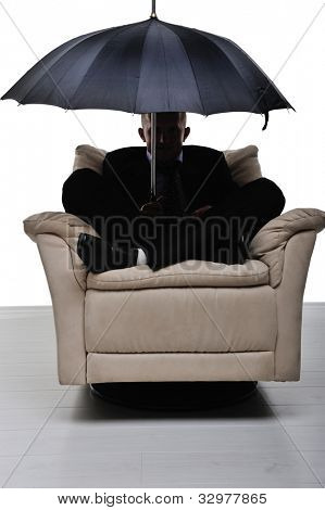 Image of a businessman sitting in comfortable armchair with an umbrella in his hand. Anonymous man.