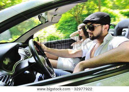 Beautiful couple enjoying nature in a sports car