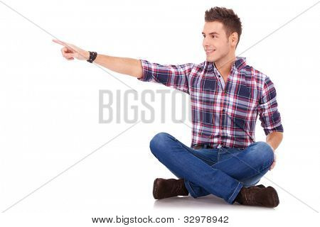 serious young man in casual clothes standing over white background with hands on hips