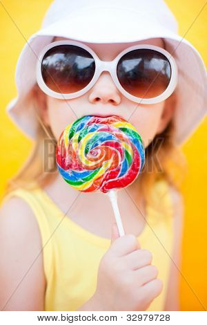Adorable little girl with lollipop over colorful background