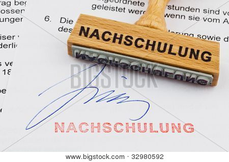 a stamp made of wood lying on a document. german inscription: retraining