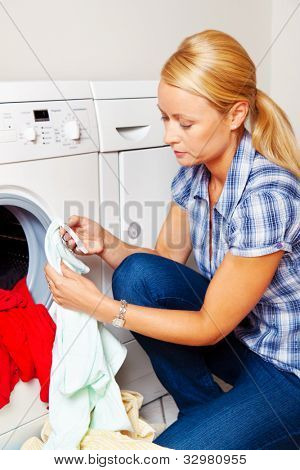 a young housewife with washing machine and clothes. laundry day.