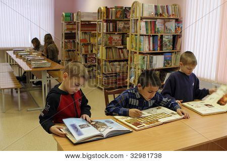 PODPOROZHYE, RUSSIA - JANUARY 31: Open Day at the Podporozhye's Children House - unknown children in the library read books with teachers, January 31, 2010 in Podporozhye, Russia.