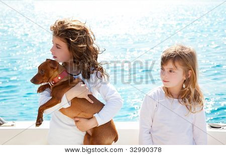 sister kid girls with dog mini pinscher on the sea view from a boat