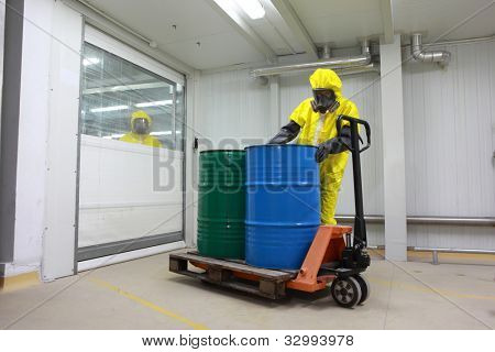 Worker in protective uniform,mask,gloves and boots working with barrels of chemicals on forklift ,another is observing hi,