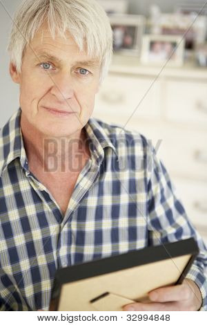 Senior man with photographs at home