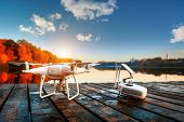 Drone copter with digital camera, blur river on autumn background poster