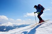 Sportsman Skier In Skiing Equipment With Backpack Jumping In Air Down Steep Snowy Mountain Slope On  poster