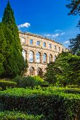 Ancient Roman Arena In Pula, Istria, Croatia, Historic Amphitheater Landscape View Through The Trees poster