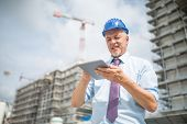 Site manager using his tablet in front of a construction site poster