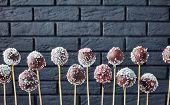 Festive Chocolate Cake Pops Sprinkled With Crushed Candies And Coconut Sprinkles With A Black Brick  poster