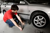 picture of auto repair shop  - A male jacks up a car in a garage  - JPG