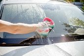 Male Hand With Tool For Washing Windows, Car Wash.man Washing A Soapy Blue Car With Colorful Sponge. poster