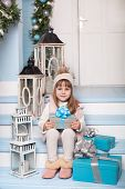 Merry Christmas, Happy Holidays! New Year 2020. Little Girl Sits With Gifts On Porch Of House Decora poster
