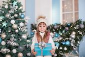 Merry Christmas, Happy Holidays! New Year. Little Girl With A Gift On  Porch Of House Near Christmas poster