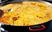 Paella rice typical from Valencia Spain cooking in big pan