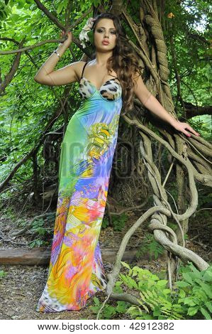 Beautiful brunette model posing pretty at tropical jungle wearing designers colorful dress