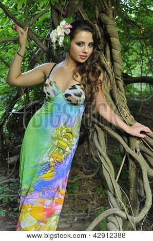 Beautiful brunette model posing pretty at tropical jungle wearing designers colorful dress