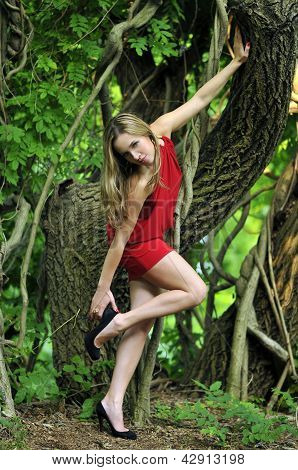 Beautiful young woman is leaning against a tree in the rain forest